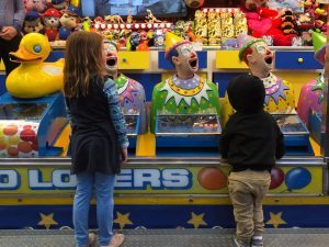 Children in front of laughing clowns fairground game