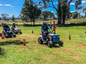 Ride on lawn mowers from Mower Mania racing on bright green grass on a sunny day