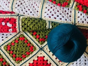 Crocheted blanket with ball of blue yarn sitting on top of it