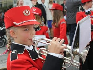 Young school girl with a red uniform playing a brass instrument