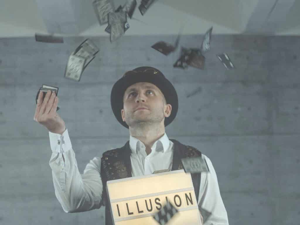 """A male illusionist throwing cards in the air and holding a board saying """"ILLUSION"""""""